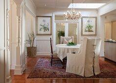 Sessel mit heller Husse und Stühle um Tisch mit Tischtuch, darüber Kronleuchter in traditionellem elegantem Esszimmer