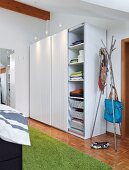 A storage solution on a bedroom consisting of a simple cupboard with sliding doors and spotlights next to a hat stand