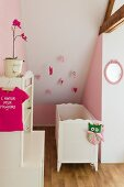 White cot in girl's nursery in converted attic