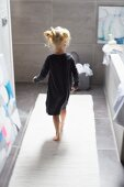 Little girl on white bathmat in bathroom