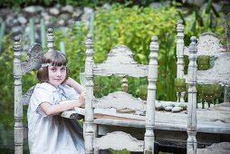 Girl sitting at white wooden table in garden