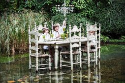Children sitting at chair in middle of pond