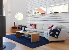 White sofa combination with stars and stripes cushions and blankets below ribbon window in wood-clad wall and porthole in background