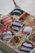 Striped, crocheted Easter eggs nestled in hay in box