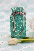 White tulip in front of bottle with hand-crocheted cover and ribbon