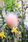 Hen's egg decorated with white feathers in Easter bouquet