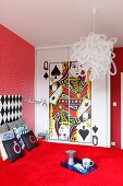 Bold, red bedroom with playing card motif on front of fitted wardrobes