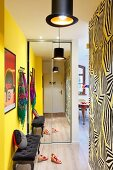 Mirrored wardrobe and antique upholstered bench in hallway with one yellow wall and wallpaper with graphic pattern