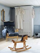 Rocking horse, armchair with grey sheepskin blanket and white farmhouse cupboard in corner of rustic room