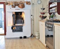 Rustic kitchen with plain wooden floor and basket hung over bricked-in, wood-fired oven