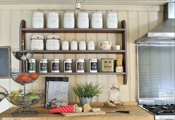Retro storage jars in spice rack on cream wooden wall