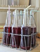 Drinking straws in bottles of cranberry juice in rustic wire bottle carrier