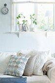 Sofa mit Kissen in verschiedenen Weissstönen vor pastellblau getönter Wand, unter Fenster