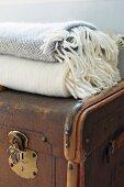 Alte Truhe mit Messing Schliessbeschlag und Wolldecken