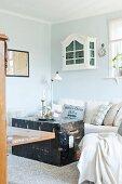 Alte Truhe vor hellem Sofa mit Kissen, darüber kleines Schränkchen in Weiss, an pastellblauer Wand aufgehängt