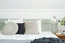 Verschiedene Kissen in Weiss- und Grautönen auf Bett, an grau lackiertem Holz Kopfteil