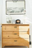 Retro birdcage, cake stand and frame black and white photo on pale, wooden chest of drawers