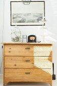 Retro Vogelkäfig und Etagere auf heller Holzkommode vor Wand mit gerahmtem Schwarzweiss Foto