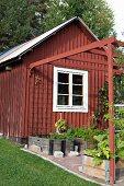 Rotbraun gestrichenes Holzhäuschen, davor Pergola mit Pflanztrögen aus Holz auf Terrassenboden