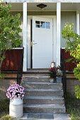Ausschnitt eines Holzhauses mit weisser Haustür, vor Veranda Steintreppe mit Blumentöpfen, an der Seite Milchkanne mit rosa Chrysanthemen