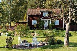 weiße Outdoor Stühle auf gekiester Fläche in sonnenbeschienenem Garten, im Hintergrund Landhaus mit rotbraun gestrichener Holzfassade