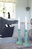 Metal candlesticks painted turquoise on wooden surface