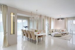 Luxurious, white interior with glossy tiled floor; dining set with postmodern table and upholstered chairs, sofa combination in background
