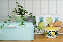 Potted ivy on pastel blue bread bin next to tray with pineapple motif and retro china pot