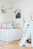 Indoor teepee in pastel shades next to cosy seating area with scatter cushions below stag's antlers and picture