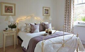 Wrought iron bed decorated with fairy lights in simple bedroom