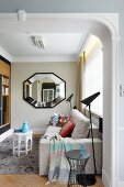 View through wide, open doorway of modern pale couch, black standard lamp and octagonal mirror