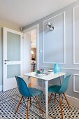 Classic chairs with blue and grey shell seats around white breakfast table in front of panelled wall with white moulding on geometric, tiled floor