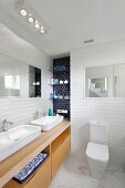 Long washstand with twin sinks on wooden base unit in white-tiled bathroom with marble floor