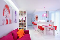 Modified portraits on wall above magenta sofa; white, open-plan kitchen and dining area with red chairs and accessories in background