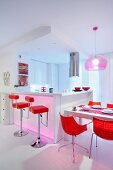Bright red shell chairs and bar stools at white dining table and kitchen counter