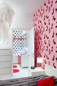 Bed against wall with shoe-patterned, pink wallpaper, view into ensuite bathroom with black polka-dot wall