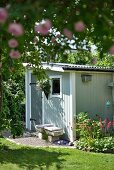 Small shed painted grey and stone bench in summery atmosphere