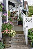 Blühende Blumen im Pflanzentrog vor Treppe zur Veranda, mit weissem Holzgeländer