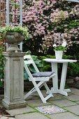 Bepflanzte Amphore auf Sockel neben weißem Gartenstuhl mit Tisch auf Terrasse