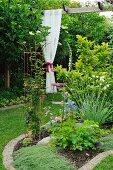 Blumenbeet im Garten, im Hintergrund geraffter weißer Spitzenvorhang an Pergola aufgehängt