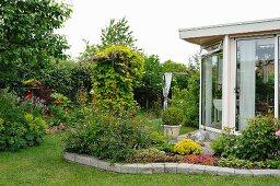 Sommerlicher Garten mit Staudenbeet vor Wintergartenanbau