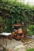 Rostige Metallgitter als Rankhilfe, Regal mit Tontöpfen vor hoher Gartenhecke