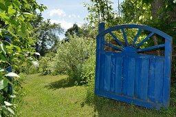 Blaues, offenes Vintage Holztor in sommerlichem Garten