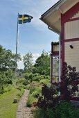 Gepflasterter Gartenweg an weissem Holzhaus vorbeiführend und Fahnenmast mit schwedischer Flagge