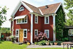 Rotbraun gestrichenes Holzhaus mit weissen Fenstern, davor gekieste Fläche mit Blumentöpfen und Azalea