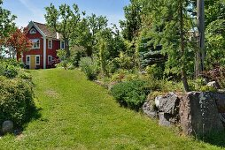 Breiter Rasenweg in sommerlichem Garten, im Hintergrund rotbraun gestrichenes Holzhaus