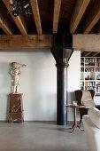 Loft-Wohnung mit Holzbalkendecke und schwarzer Metallstütze, seitlich Skulptur auf Sockel und Beistelltisch vor Lesesessel