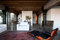 Klassiker Lounge Chair und weisser Sessel in Loft-Wohnbereich mit Industrie Charme, im Hintergrund rustikaler Essplatz