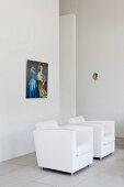 Weisse Designersessel vor Wand mit aufgehängtem Bild, in minimalistischem Ambiente