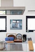 Ausschnitt einer Theke, Messerblock neben Kochfeld, im Hintergrund Küchenutensilien auf Ablage, vor Wand mit aufgehängtem Bild